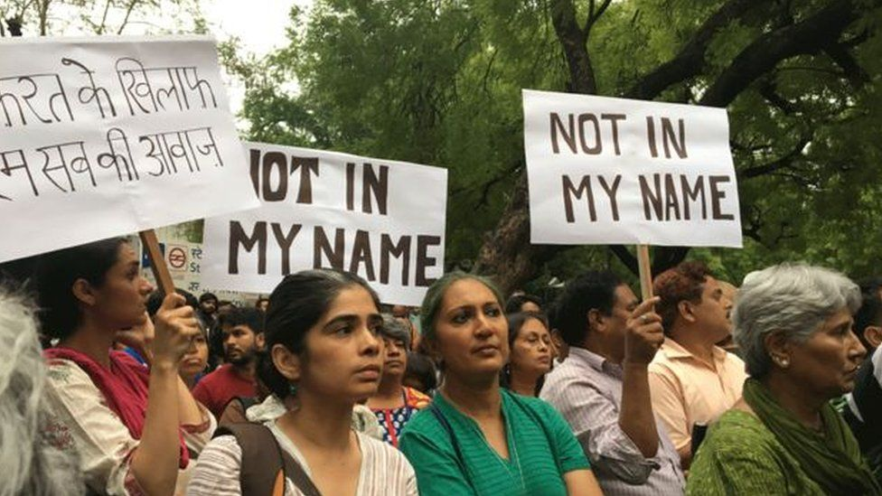 """People protesting against cow vigilante groups with signs that read """"not in my name"""""""