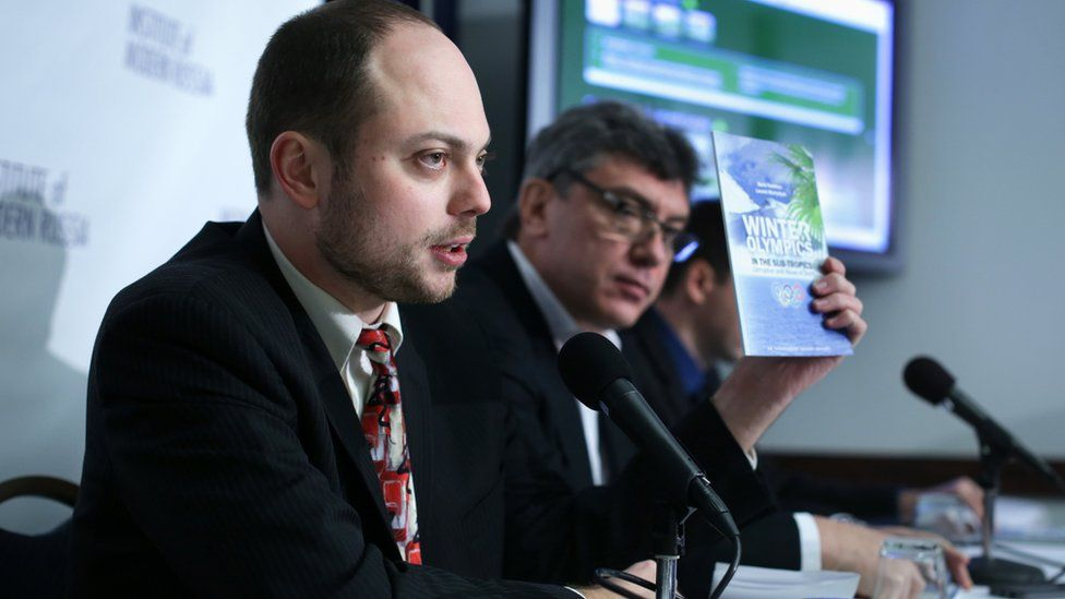 """Vladimir Kara-Murza holds up a copy of the report on """"Winter Olympics in the Sub-Tropics"""" as Russian opposition leader and former Deputy Prime Minister Boris Nemtsov listens in January 2014"""