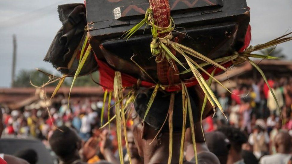 "A man carrying a ""magic"" wooden box on his head through the streets of Arondizuogu during the Ikeji Festival in Nigeria"