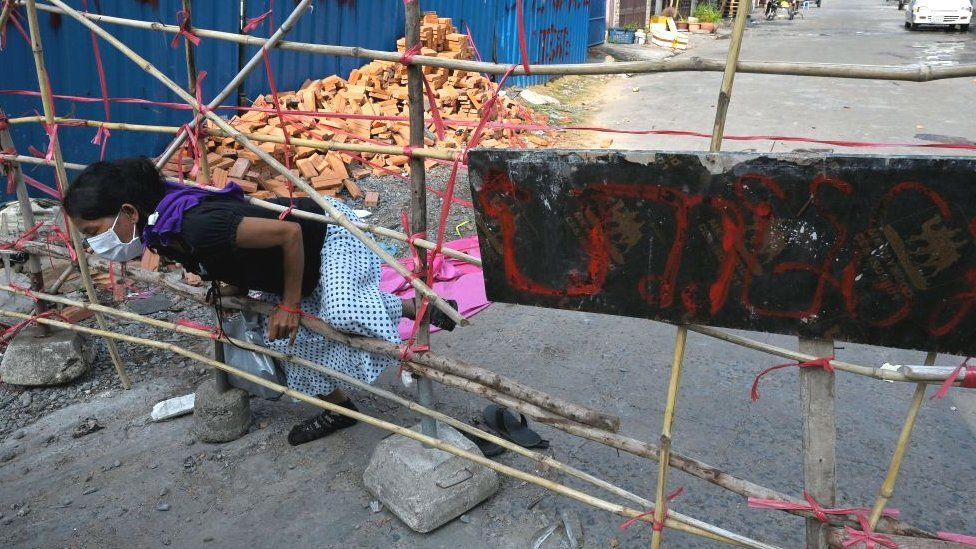 A woman in a designated red zone pushes through a barricade