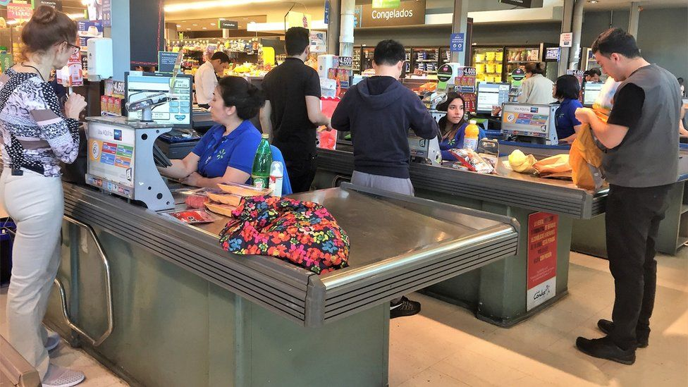 Shoppers pack their purchases into bags in a supermarket in Chile