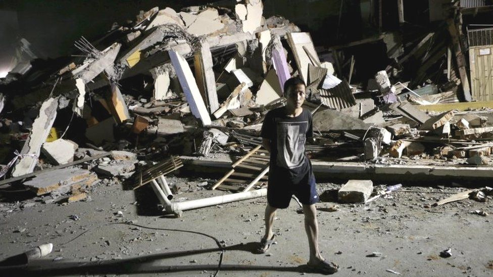 A resident walks past a collapsed hotel after an earthquake struck off the Pacific coast in Portoviejo (17 April 2016)