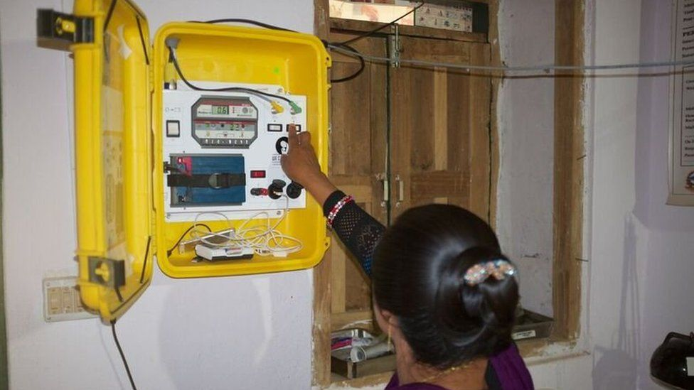Midwife Hima Shirish switches on yellow suitcase fixed to wall housing mobile solar power station