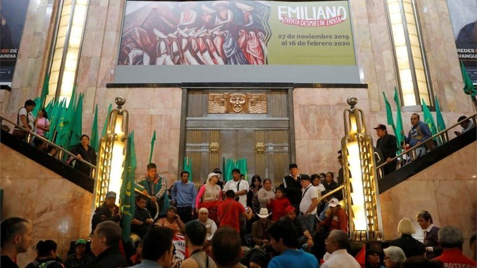 A group of people block the entrance of the Fine Arts Palace to protest against a painting showing Mexican revolutionary hero Emiliano Zapata in Mexico City