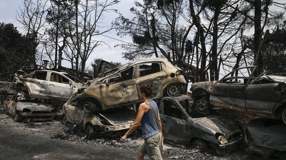 A woman walks past the burnt cars after wildfires hit the village of Mati near Athens, Greece on July 24, 2018
