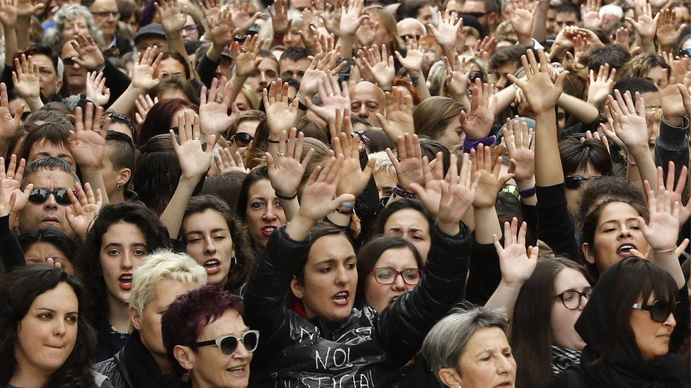 Protesters raise their arms in Pamplona on April 28, 2018, in the third day of demonstrations after five men were cleared of rape