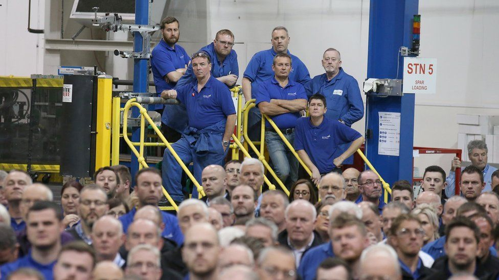 Workers look on as Scottish First Minister Nicola Sturgeon makes a keynote speech