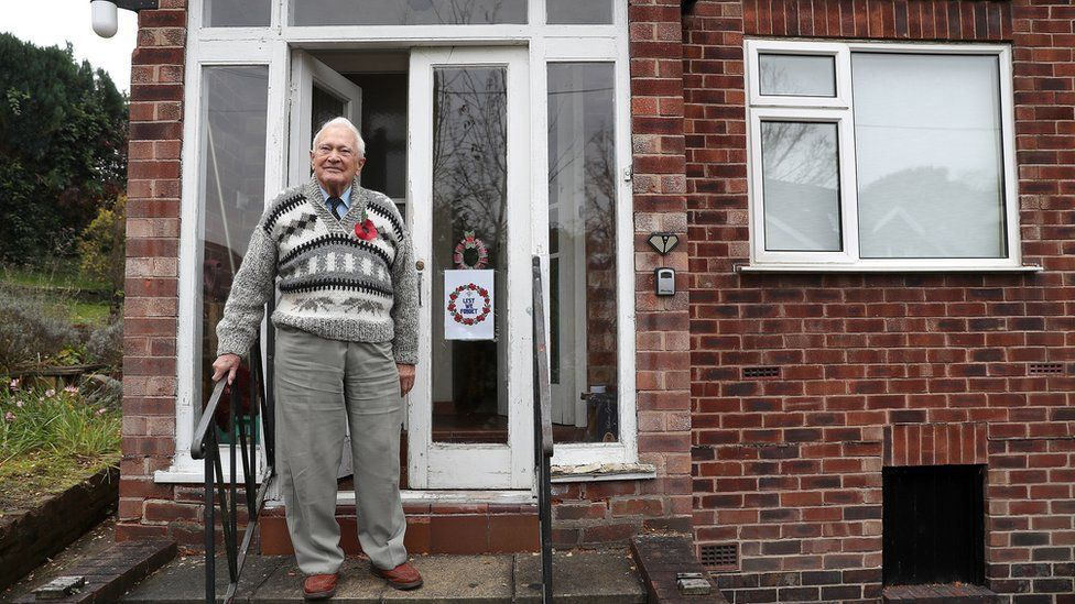 World War Two veteran John Maffey 93, stands on his doorstep in Knutsford, Cheshire, during the two minutes silence