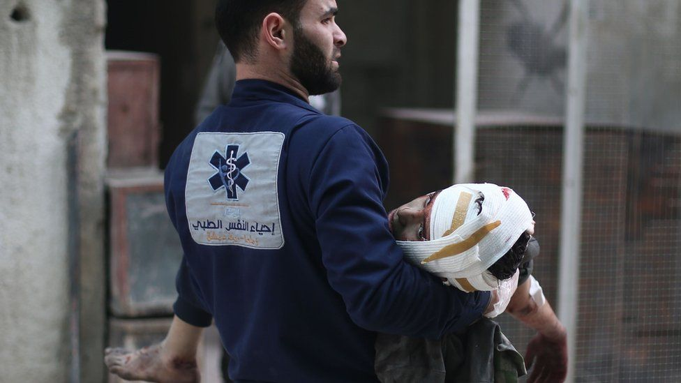 A medic carries an injured person in the rebel-held town of Zamalka, in the Eastern Ghouta (5 February 2018)