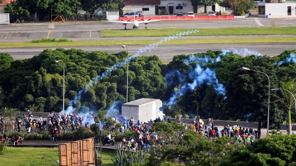 Demonstrators clash with riot security forces in front of the fence of an air base while rallying against Venezuela's President Nicolas Maduro in Caracas, Venezuela, May 31, 2017.
