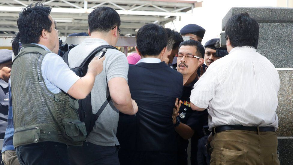 """Journalists scuffle with a police officer as they try to interview a North Korea official at the morgue at Kuala Lumpur General Hospital where Kim Jong Nam""""s body is held for autopsy in Malaysia February 15, 2017"""