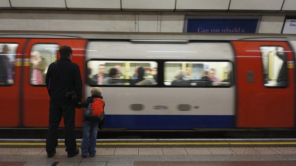 A parent and child wait as a Tube arrives