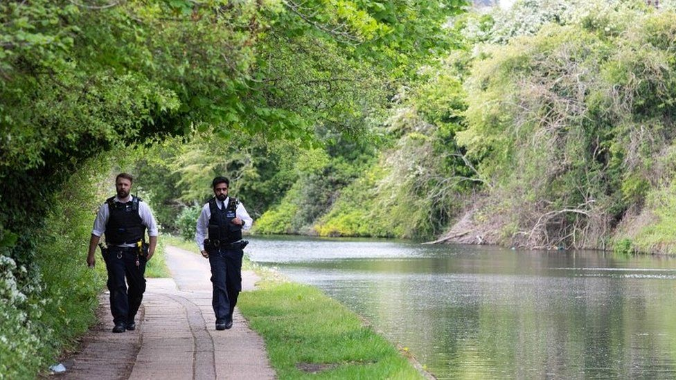 Police officers beside canal