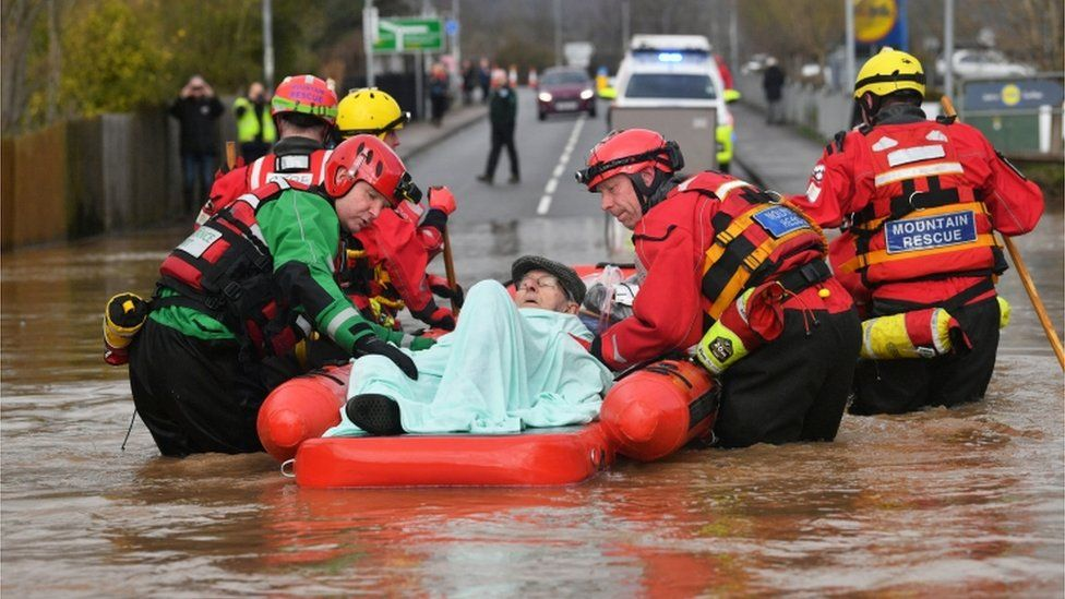 Rescuers help Peter Morgan in a boat