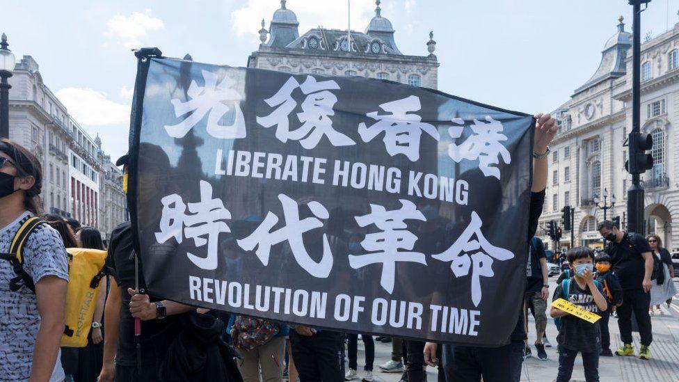Protestors hold up a banner that says Liberate Hong Kong