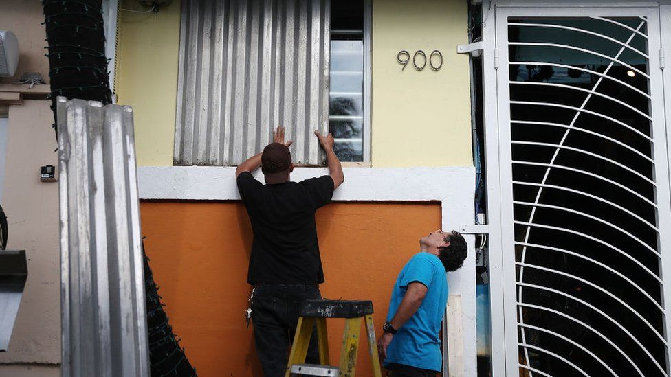 Workers place hurricane shutters over windows in Florida