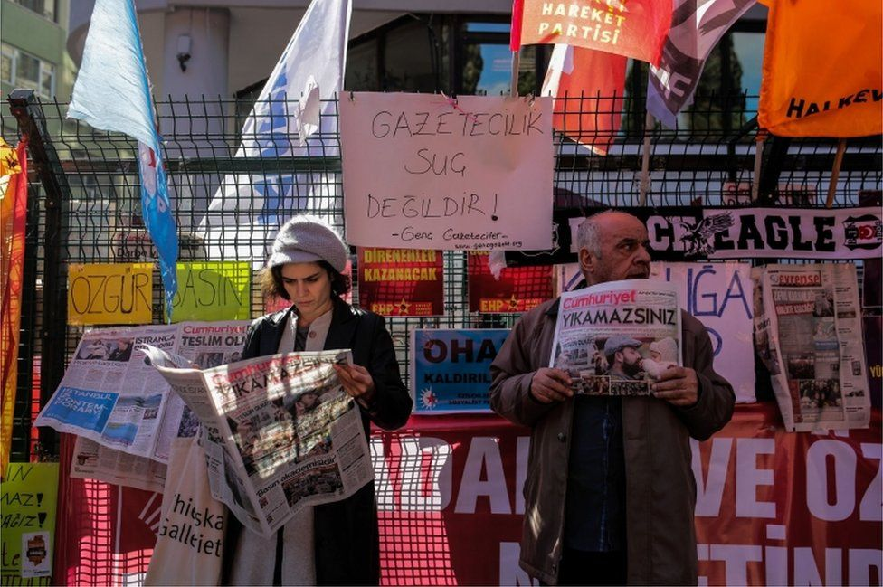 """A protester holds a copy of the Turkish daily newspaper """"Cumhuriyet"""" next to a woman reading it during a demonstration outside the newspaper""""s headquarters in Istanbul on November 2, 2016."""