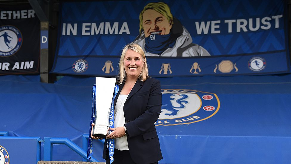 Emma Hayes lifting trophy with fan banner behind