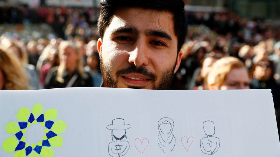 A man holds up a sign featuring symbols of different religions during a memorial ceremony at Sergels Torg plaza in Stockholm, Sweden on 9 April 2017