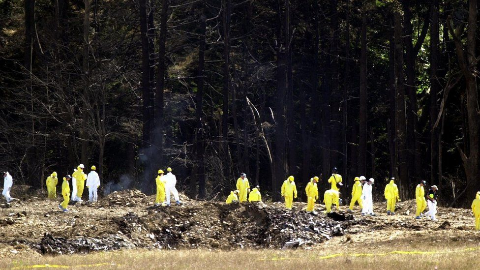 Investigators comb the debris field for the flight data recorders from United Airlines Flight 93 near Shanksville, Pennsylvania, September 12, 2001