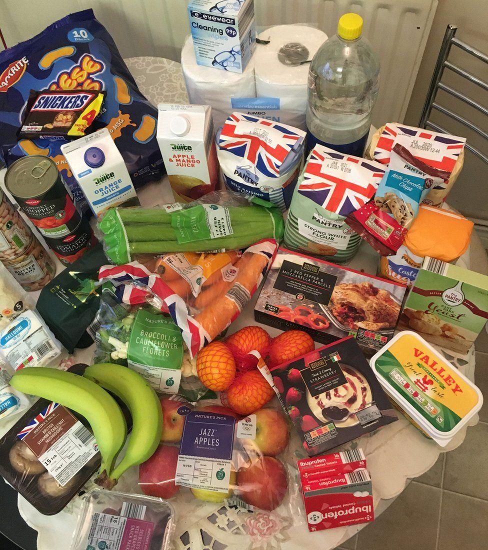 A table full of shopping: bananas, flour, toilet roll, etc