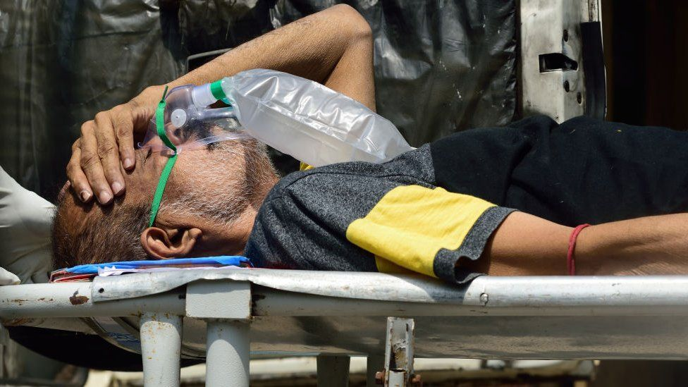 A Covid-19 patient wearing a medical oxygen mask being carried on a stretcher into a hospital before admission as pandemic situation has drastically deteriorated in the county in Kolkata, India on April 24, 2021