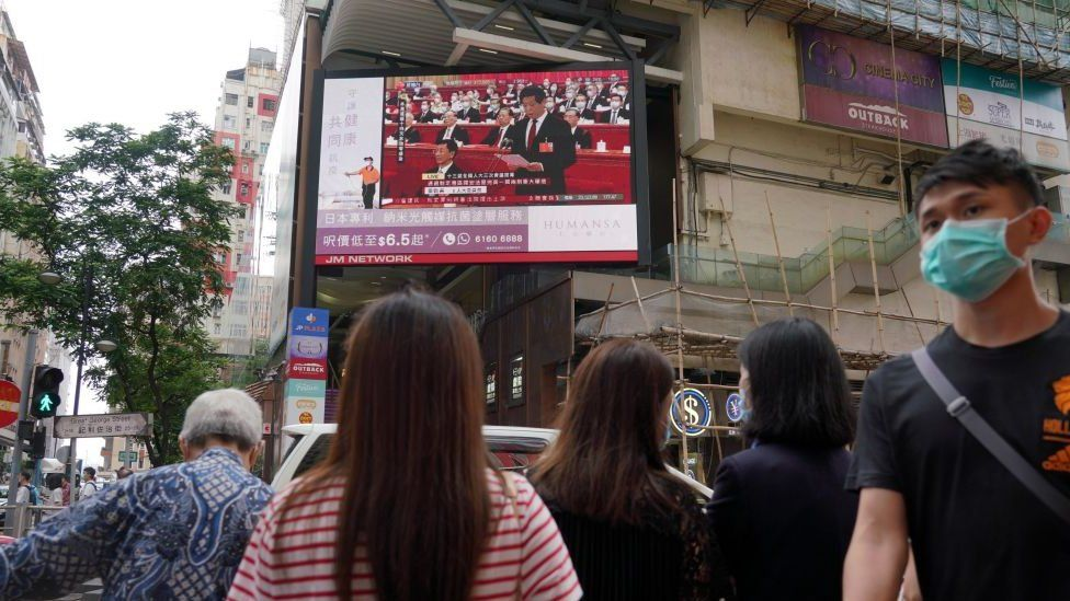 People wearing face masks walk past a large screen in Hong Kong displaying a live broadcast in the street of the National Congress