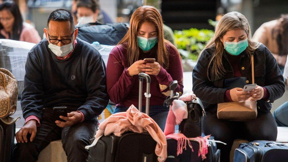 Passengers wear face masks to protect against the spread of the Coronavirus as they arrive on a flight from Asia at Los Angeles Airport