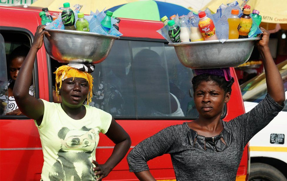 Women carrying drinks on their heads watch as the motorcade that carries the media covering U.S. first lady Melania Trump passes in Accra, Ghana, October 2, 2018