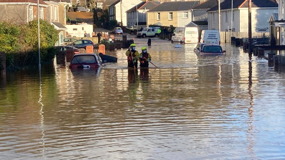 Firefighters waded through water up to their thighs amidst reports of evacuated homes in Skewen
