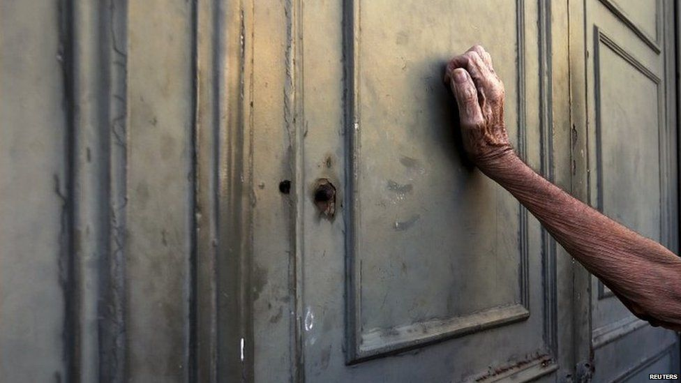 Greek pensioner leans on the entrance to the National Bank waiting to receive payment, 7 July 2015
