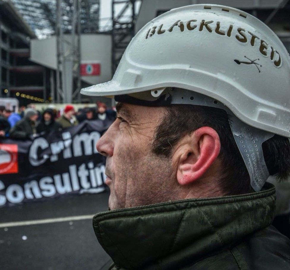 """A Blacklist campaigner wearing a hardhat declaring he had been """"blacklisted"""""""
