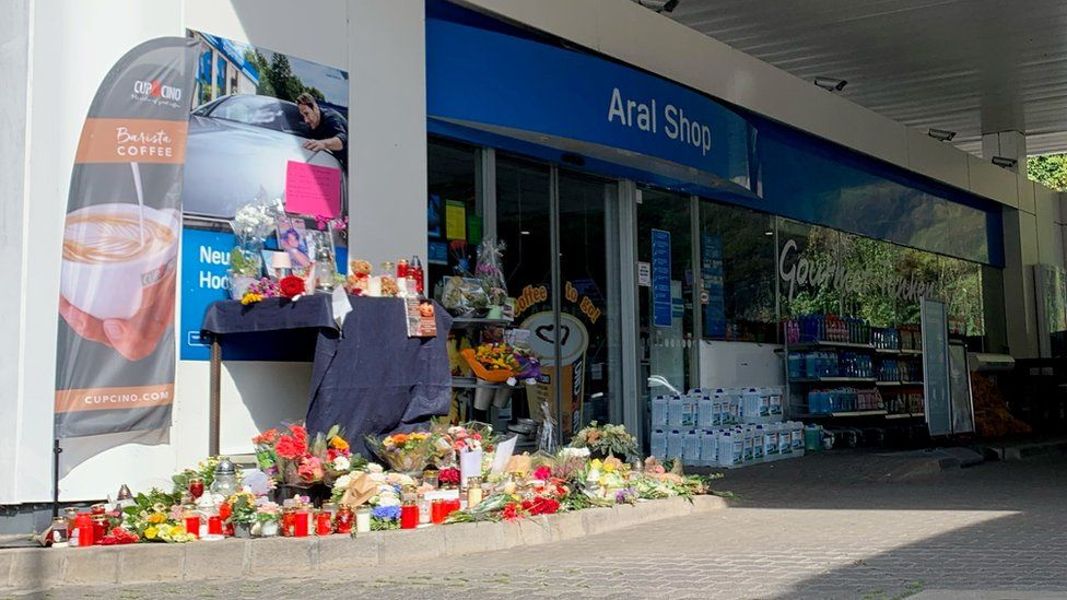Flowers are placed in front of a gas station in Idar-Oberstein, Germany, September 21, 2021, after a 20-year-old gas station attendant who asked a customer to wear a face mask was shot dead last Saturday