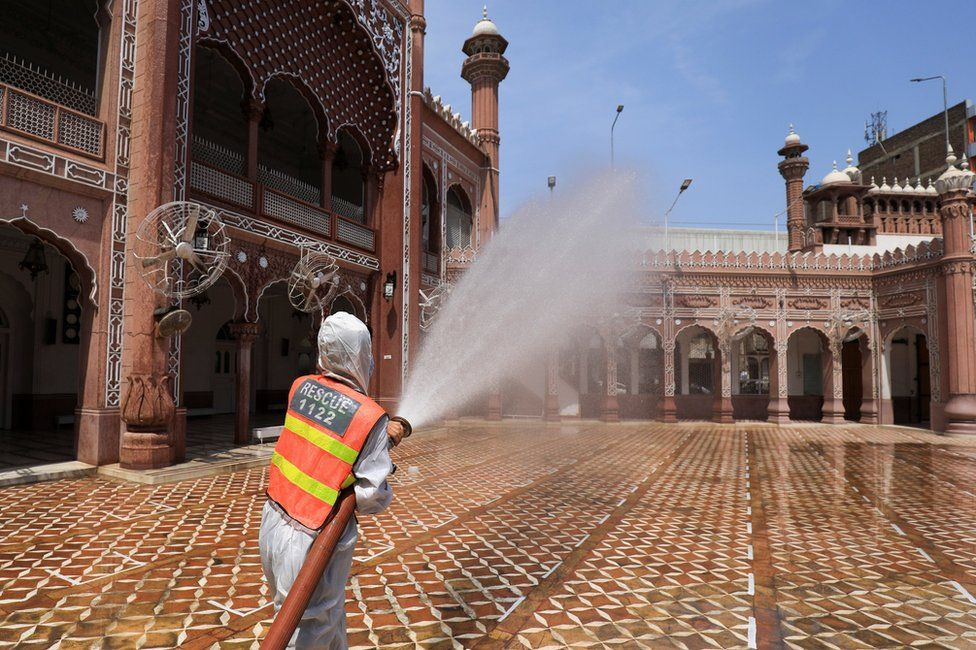 A worker sprays disinfectant from a hose at the exterior of a mosque