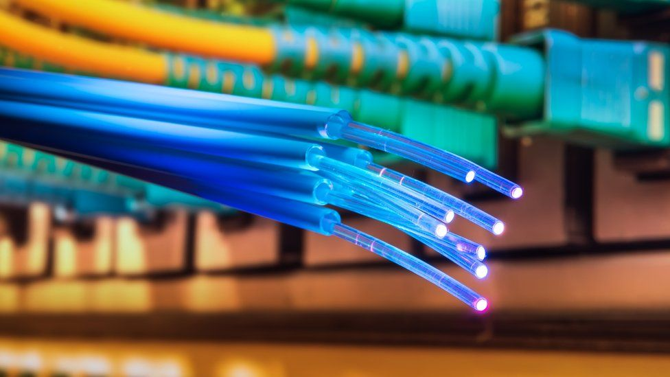 A fibre optic cable hangs loose near the ethernet ports of a server
