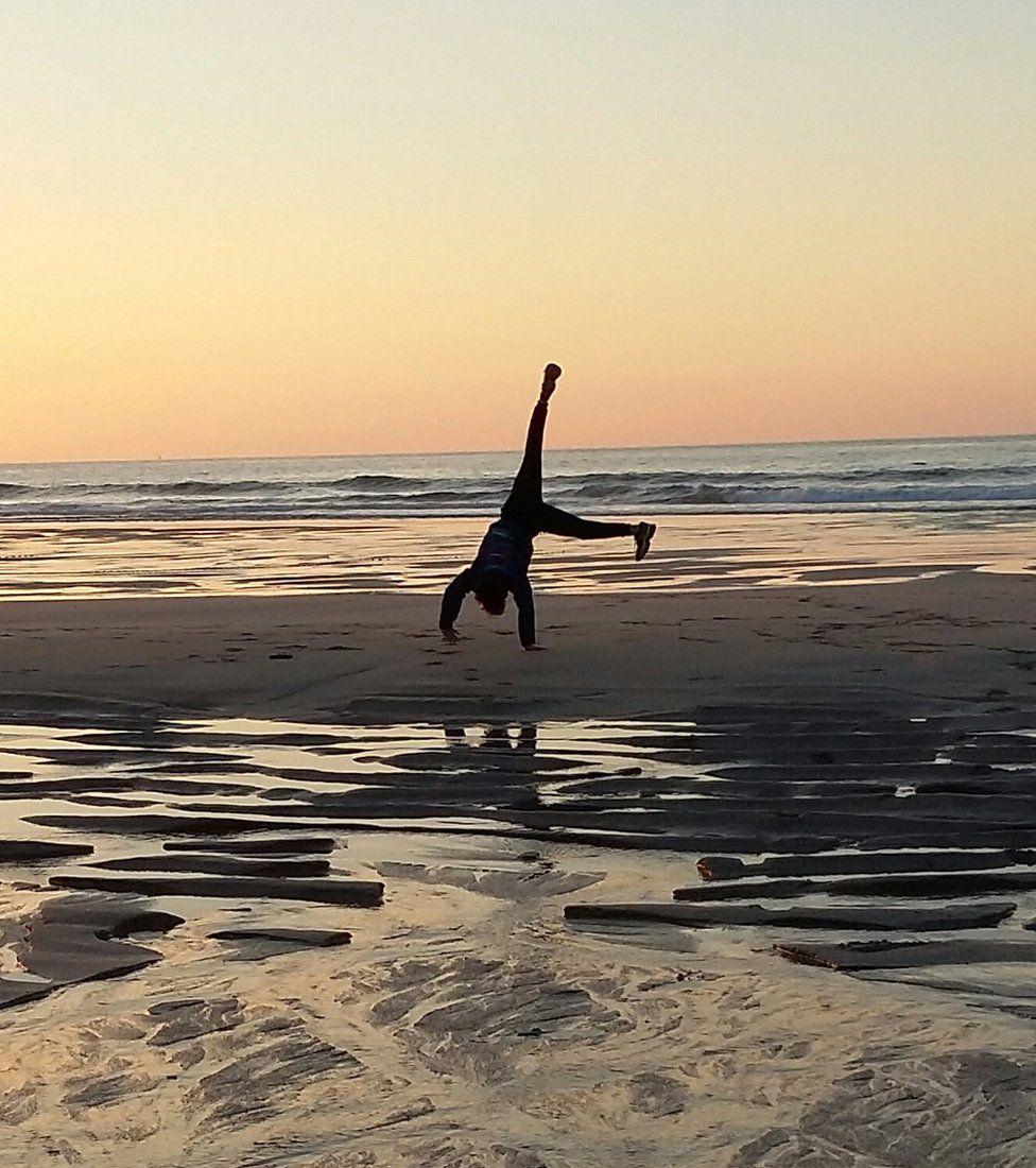 Boy doing a cartwheel on the beach