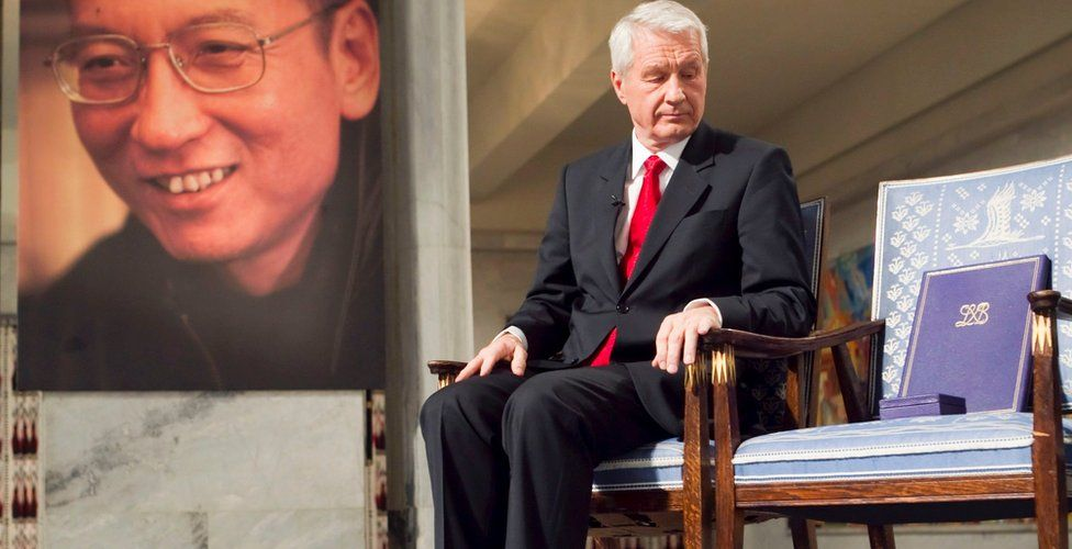 Nobel Committee Chairman Thorbjorn Jagland sitting during the Peace Prize Ceremony in Oslo in front of a photo of Nobel peace laureate Liu Xiaobo