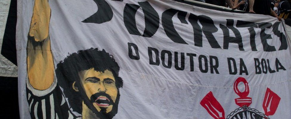 Supporters of Corinthians stand next to a banner in homage of the late footballer Socrates, during the Brazilian Championship final date match against Palmeiras, at the Pacaembu stadium on 4 December 2011 in Sao Paulo, Brazil