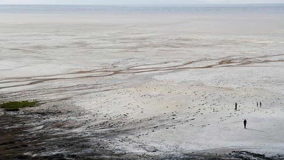 A family walks on the salt flat at Lake Urmia