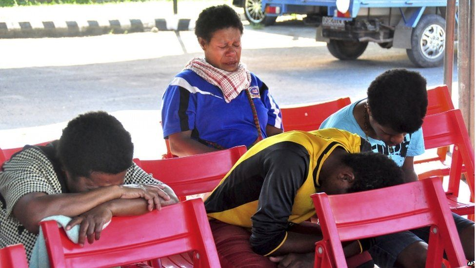 Relatives of passengers on the missing Trigana Air Service flight sit at Sentani airport in Jayapura, Papua province, Indonesia, Monday, 17 August 2015.