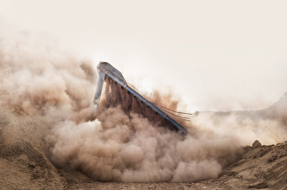 A building falls down in a cloud of dust