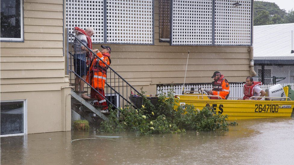 Emergency workers in a boat help rescue an elderly resident from his home in Rosslea, Townsville