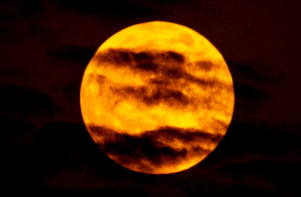 A picture of the blood man taken in Dubai, UAE, shows red-tinged clouds across a bright orange moon