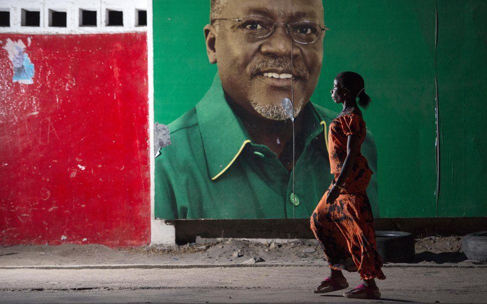 Woman walking past John Magufuli poster