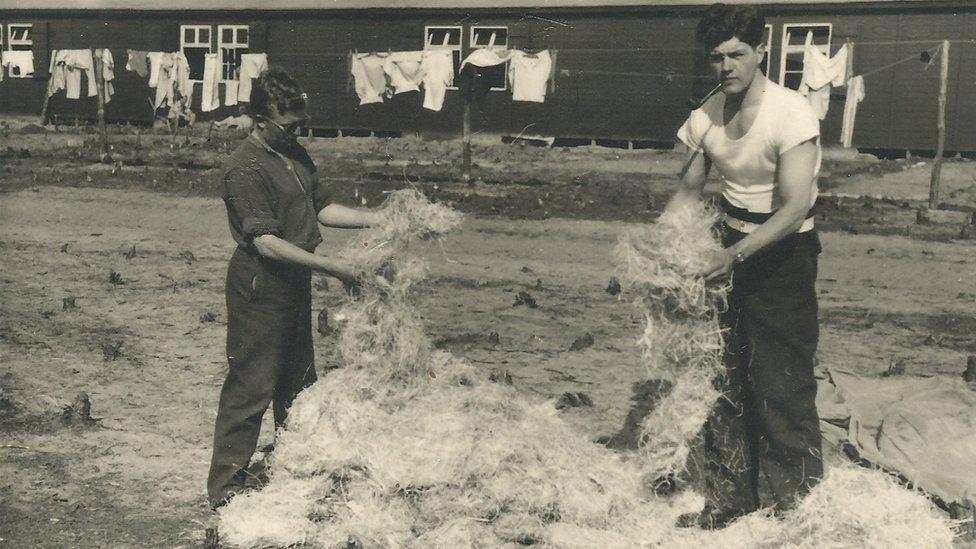 Alastair Gunn, right, stuffing fresh straw into bedding at Stalag Luft III