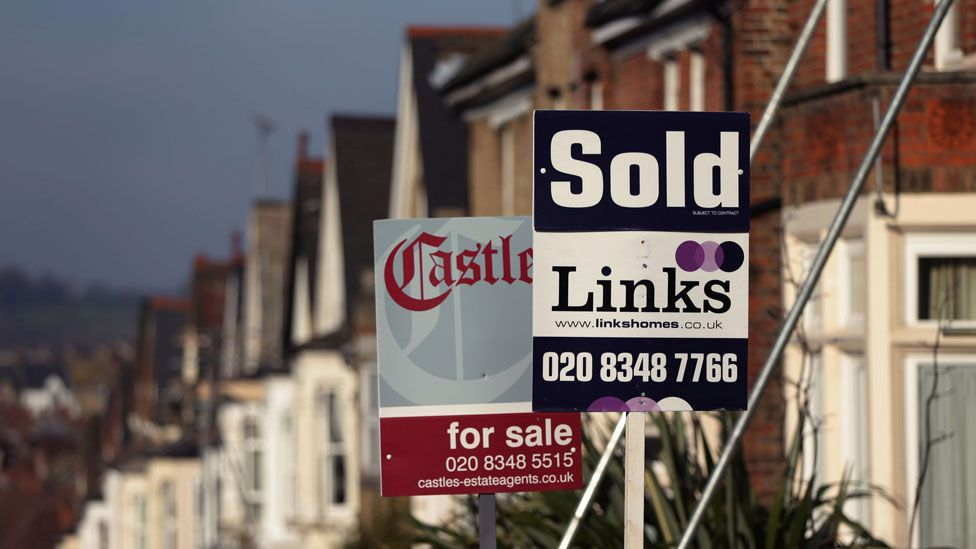 Houses in North London with for sale and sold signs outside