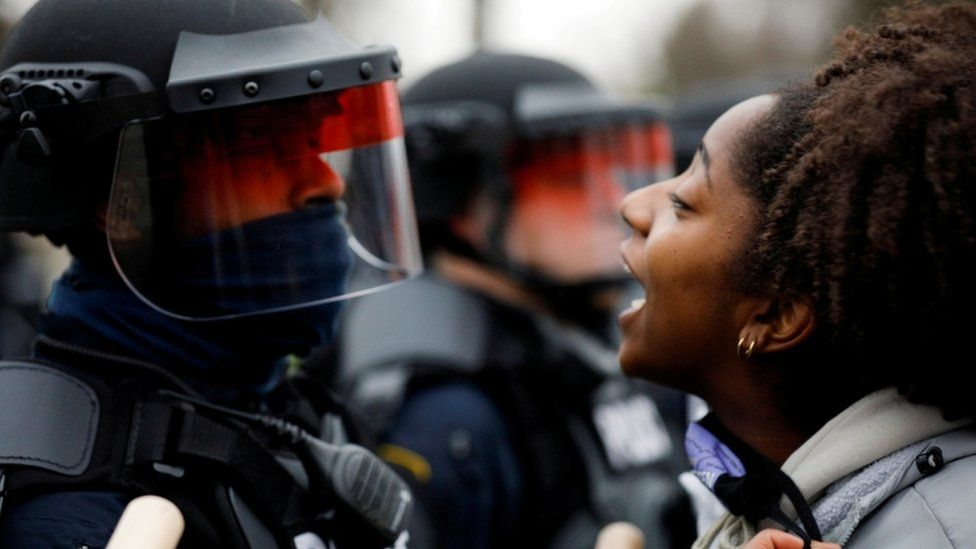 A woman yelling in the face of a police officer