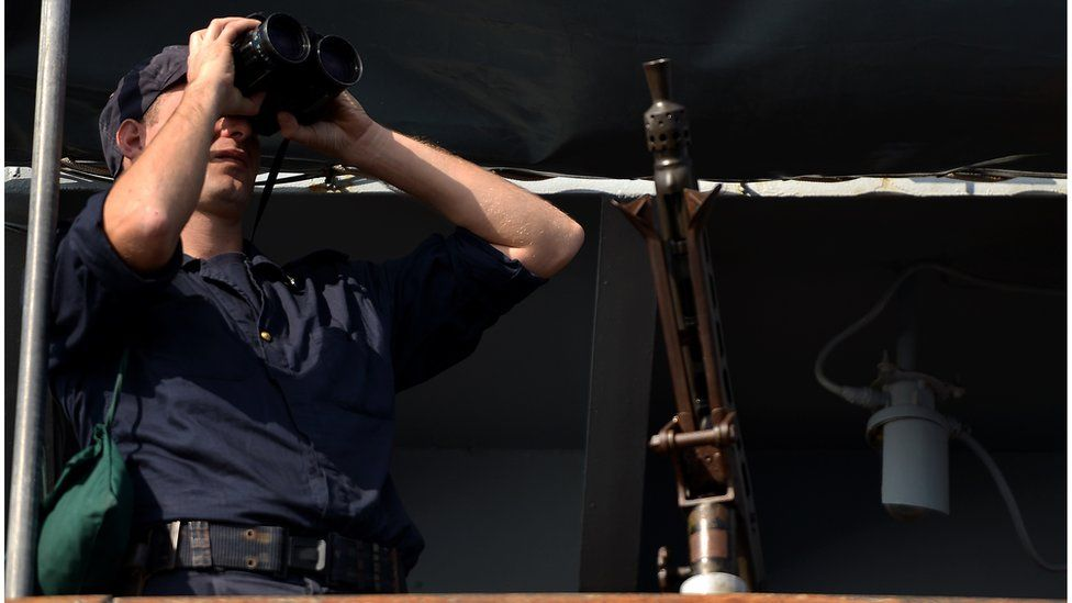 An officer looks in his binoculars onboard the Italian navy assault ship San Marco off the shores of Lampedusa island on 25 October, 2013.