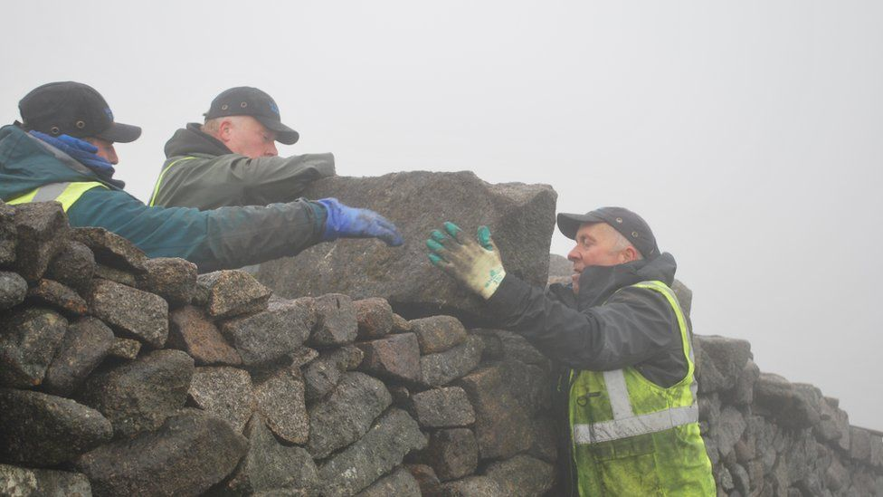 The men lift a capping stone on to the top of the wall close to the summit of Slieve Donard