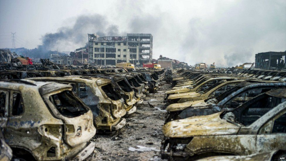 Smoke continues to billow from behind rows of burnt out Volkswagen cars following the explosion at a chemical warehouse in Tianjin, in northern China - 14 August 2015